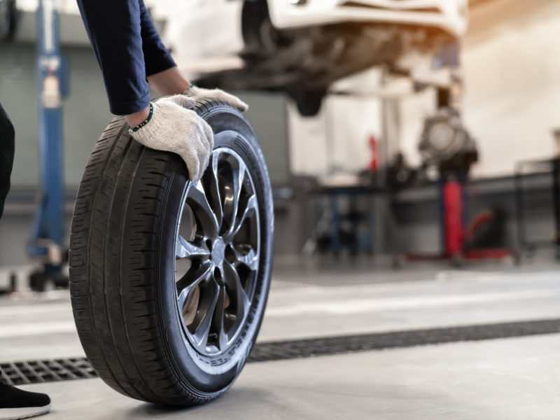 Mechanic man change a wheel tire and service maintenance the suspension of a vehicle , Safety inspection test engine before customer drive a car on a long journey, transportation service